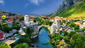 Preview wallpaper alpine, town, mountains, houses, bridge, river, trees, nature, landscape
