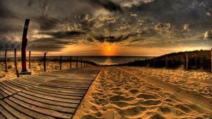Preview wallpaper beach, sand, road, traces, fence, sun, evening, sky, decline, clouds