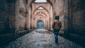 Preview wallpaper boy, street, rain, walls, arches, stone