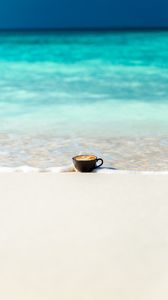 Preview wallpaper cup, ocean, sand, coast, minimalism