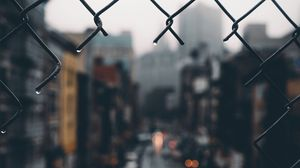 Preview wallpaper fence, grid, hole, rain, city, blur