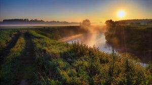 Preview wallpaper fog, haze, road, country, grass, sun, morning, dawn, river