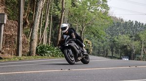 Preview wallpaper motorcycle, black, motorcyclist, speed, road, trees