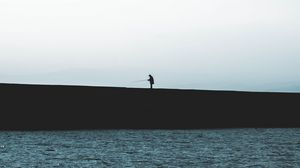 Preview wallpaper silhouette, coast, dark, sea, fisherman