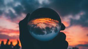Preview wallpaper ball, glass, sunset, hand, reflection