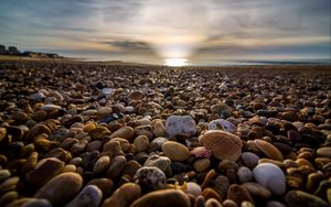 Preview wallpaper beach, pebbles, sea, stones, sky, rays