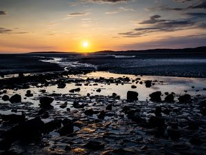 Preview wallpaper beach, sunset, water, stones, sand, sea, dusk