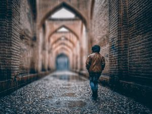 Preview wallpaper boy, street, rain, walls, arches, stone