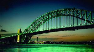 Preview wallpaper city, bridge, big, green, background, bow, lights, water, night, building, horizon, sky, clouds, orange