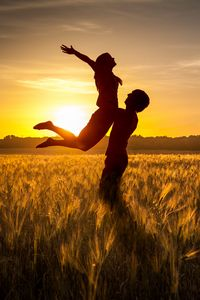 Preview wallpaper couple, love, sunset, field, grass, silhouettes