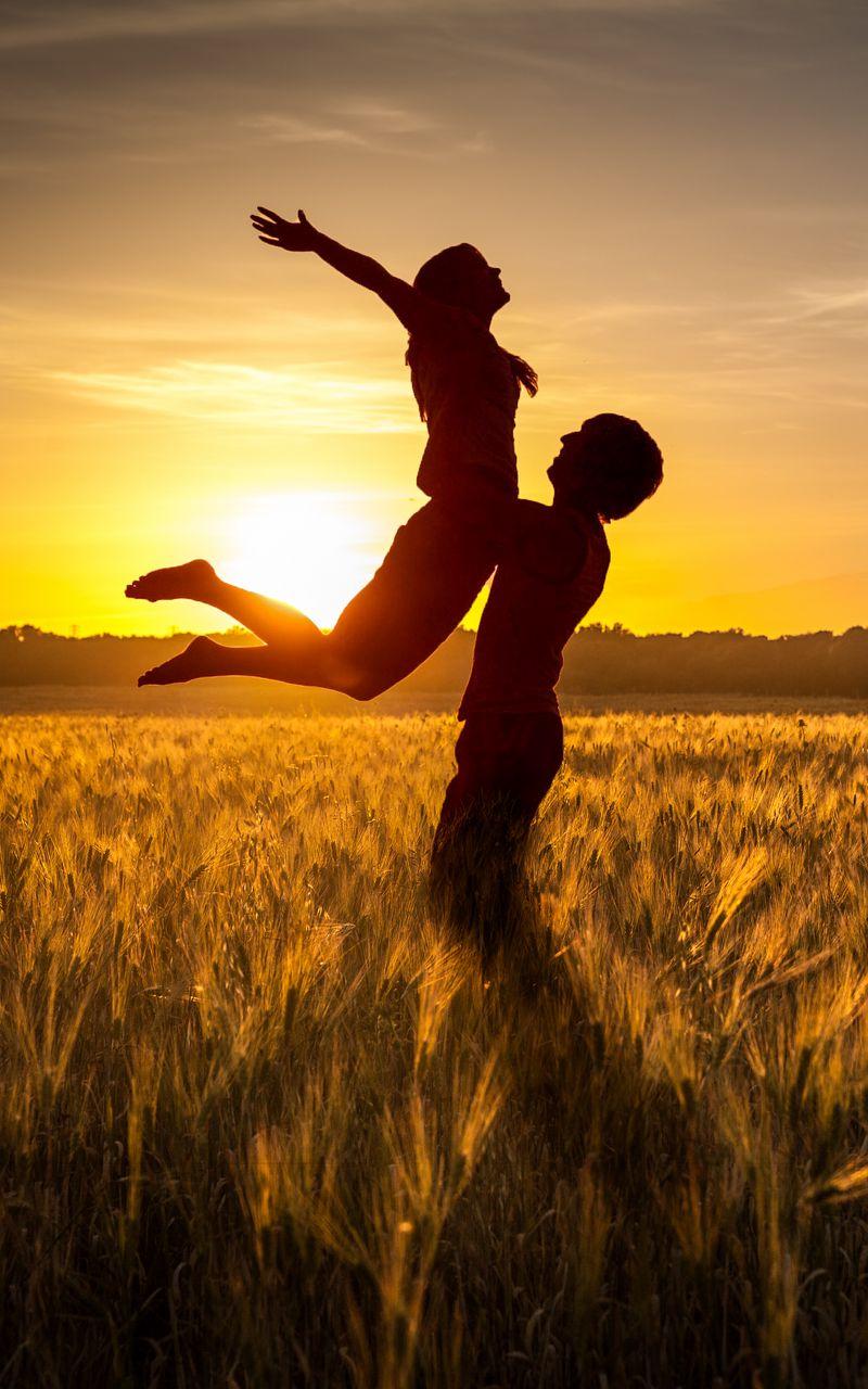 800x1280 Wallpaper couple, love, sunset, field, grass, silhouettes