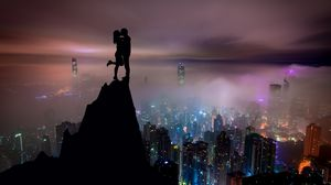 Preview wallpaper couple, silhouettes, kiss, hill, city, skyscrapers