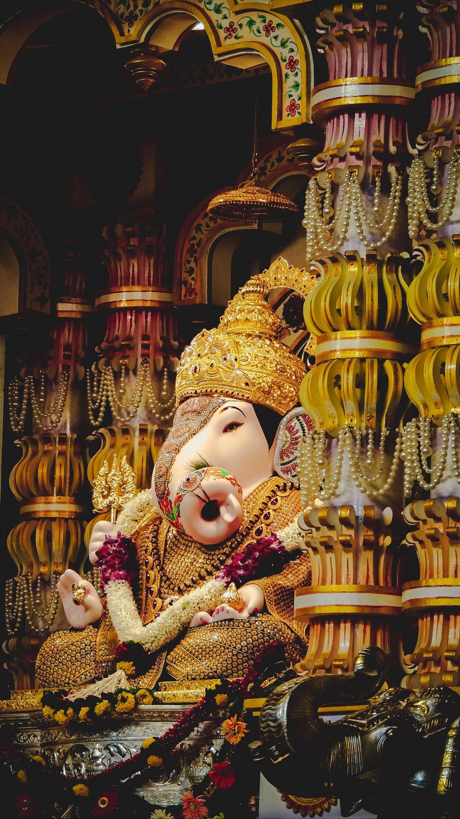 938x1668 Wallpaper ganesha, deity, god, religion, statuette, columns, golden