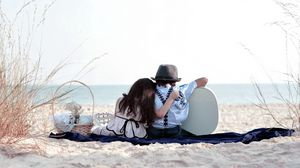 Preview wallpaper girl, sand, trash, grass, couple, date