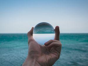 Preview wallpaper hand, ball, glass, reflection, distortion, sea