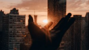 Preview wallpaper hand, rays, sun, city, sunset