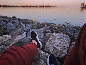 Preview wallpaper legs, sneakers, rocks, city, horizon, sea