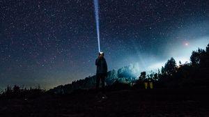 Preview wallpaper man, night, flashlight, light, ray, starry sky