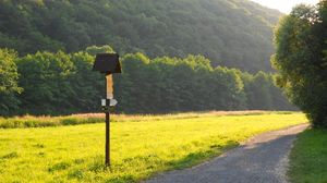 Preview wallpaper meadow, grass, road, sign, trees
