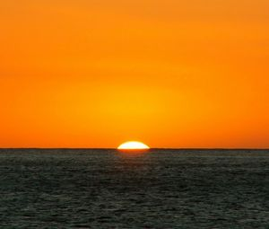 Preview wallpaper orange, dark blue, sea, horizon, sun