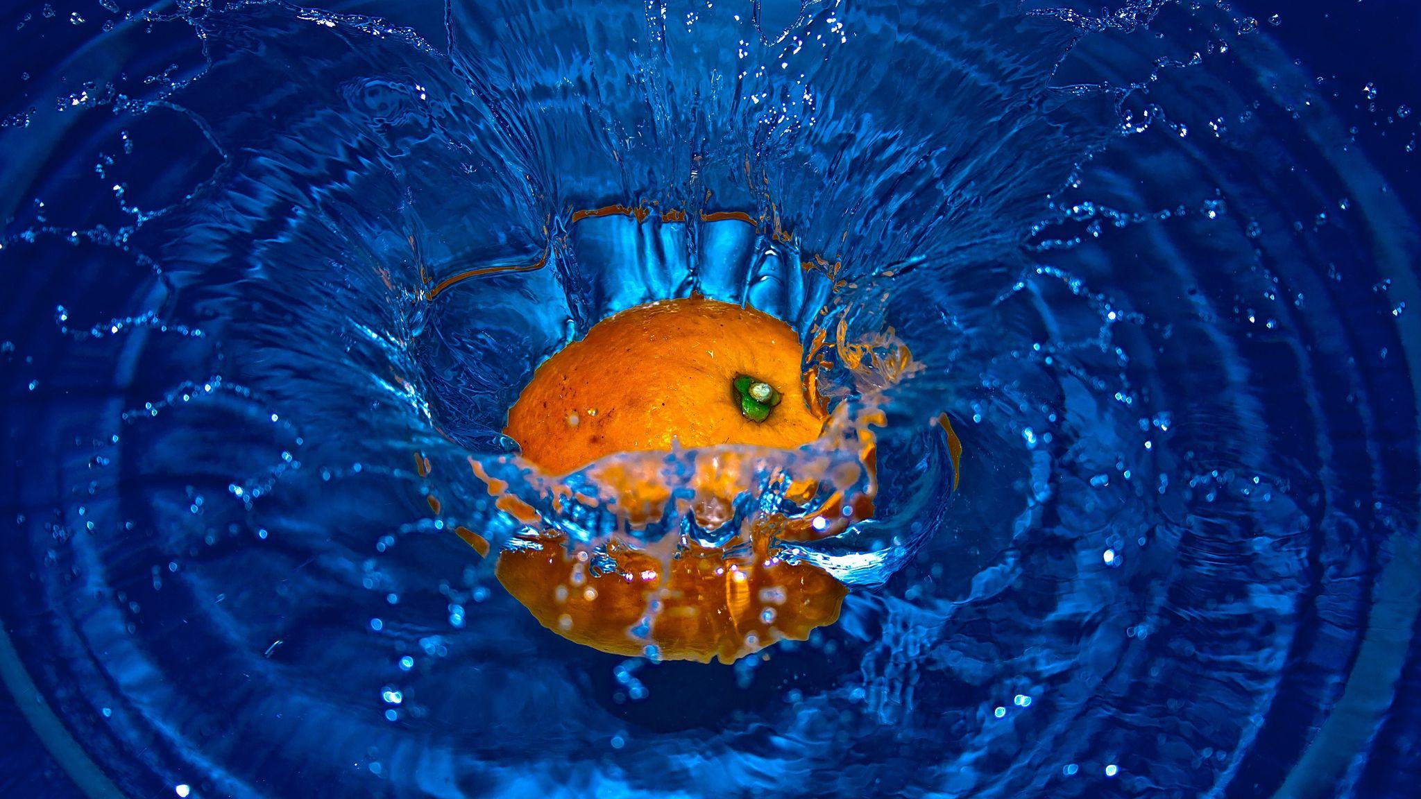 2048x1152 Wallpaper orange, spray, water, fruit, citrus