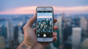 Preview wallpaper phone, hand, city, photo