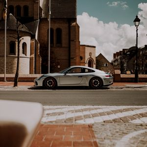 Preview wallpaper porsche, car, silver, road, buildings, architecture