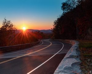 Preview wallpaper road, turn, trees, rays, sunset