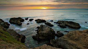 Preview wallpaper rocks, reeves, coast, sea, horizon, sun, evening, decline, emptiness, sky, grass, look, landscape