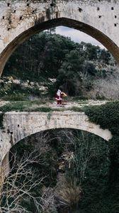 Preview wallpaper santa claus, bridge, arch, costume, bag, cliff, trees, bushes