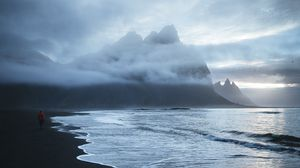 Preview wallpaper lonely, sea, beach, wave, sand, black, man, mountains, clouds