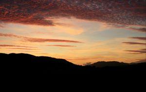 Preview wallpaper sky, clouds, sunset, hills, dark
