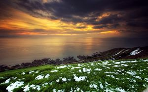 Preview wallpaper snow, grass, green, coast, sea, clouds, sky, orange, decline, anomaly