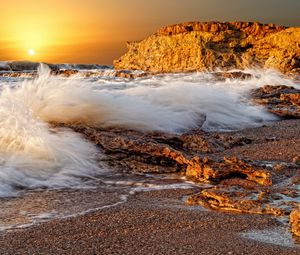 Preview wallpaper splashes, wave, splash, stones, porous, sea, rocks, coast, decline, sun, disk, orange