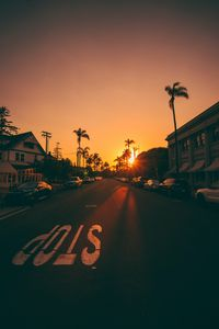 Preview wallpaper street, sunset, palm trees, road, road signs, cars
