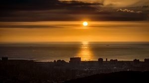 Preview wallpaper sun, sunset, coast, sea, city, dark