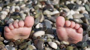 Preview wallpaper summer, sea, legs, pebble, beach, funny, situation